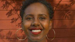 En leende kvinna med brun hud.