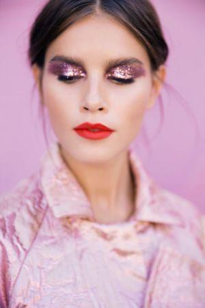 En kvinna med slutna ögon i en rosa glittrig kimono.