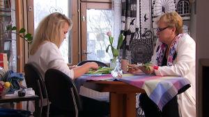 Asta ja Paula Alasimonen istuvat pöydän ääressä ja laittavat kukkia maljakkoon.