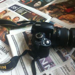 Bild på en systemkamera ovanpå tidningar.