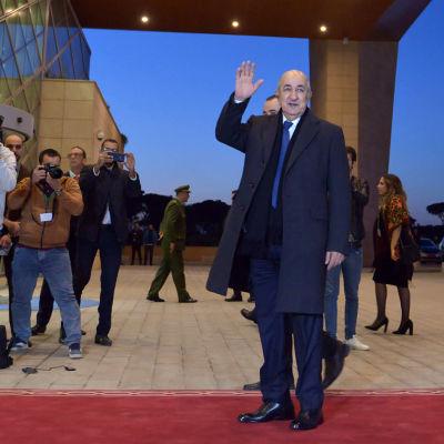 Algeriets president Tebboune vinkar till kameran. Till vänster flera fotografer.