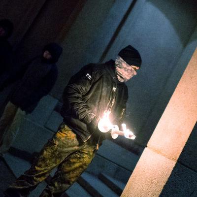 En man som är medlem i Nordiska motståndsrörelsen står med två brinnande facklor i handen i samband med 612-fackeltåget.
