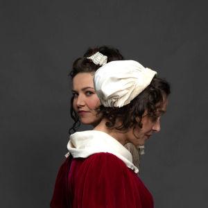 Julia Korander och Nina Hukkinen i fotosession i 1700-talsdräkter. Julia tittar mot kameran, Nina tittar bort.