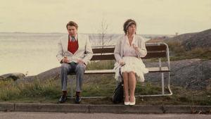 Nainen ja mies istuvat samalla puistonpenkillä, mutta hieman etäällä toisistaan. He syövät jäätelöä. Ilma vaikuttaa kylmältä.