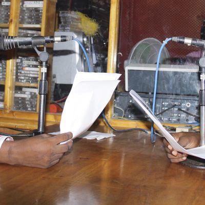 kaksi miestä lukevat radiosähkeitä.