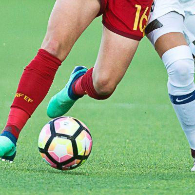 Jalkapallokenttä, pallo ja kahden pelaajan jalat.