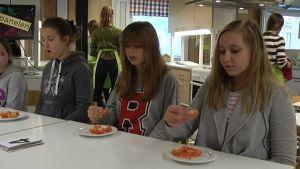 Tre tjejer smakar på tomat er