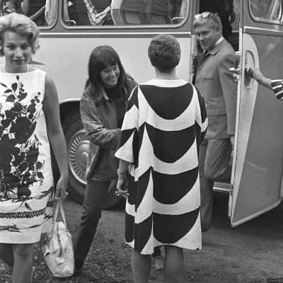 Rapujuhlat Armi Ratian loma-asunnolla Bökarsissa. Armi Ratia Marimekon puvussa vastaanottaa linja-autosta laskeutuvia vieraita.