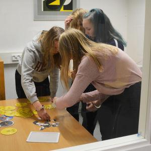 Fyra flickor står inne i ett litet rum och jobbar på att sätta ihop ett pussel. Bilden är tagen genom ett fönster i väggen.