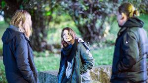 Matleena Kuusniemi istuu kivetyksellä Tommin ja Santerin seistessä vierellä.