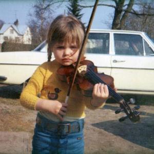 Anna-Maria Helsing som liten flicka med en fiol på axeln.