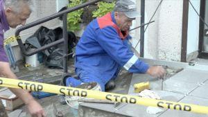 De äldre byggarbetarna Algirdas och Juozas reparerar några trappsteg.
