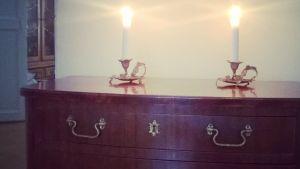 En mahognybyrå med två ljus.