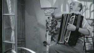 Mies soittaa haitaria mustavalkoisessa elokuvassa.