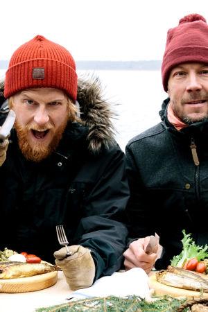 """Tom Nylund ja Mikko """"Peltsi"""" Peltola Itämeren äärellä kala-annosetn kanssa pipot päässä."""