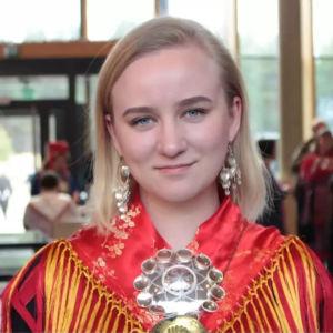 Petra Laita ler och tittar rakt in i kameran. Hon har en samisk folkdräkt på sig och silvriga örhängen.
