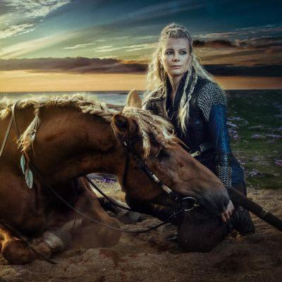 Nainen istuu hevosen vierellä rannalla auringonlaskussa. Valokuvaaja Antti Karppisen valokuva, joka jäljittelee Vikings televisiosarjan fantasiatyyliä.