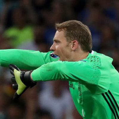 Fotbollsmålvakt viftar med armarna och skriker åt lagkamraterna.