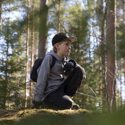 Poika istuu kivellä.