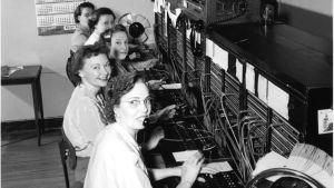 en bild av fem kvinnor som arbetade som telefonoperatörer på femtiotalet. framför sig har de paneler med kablar för att koppla samtalen med.