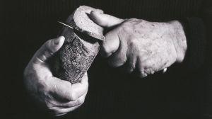 Tapio Wirkkala leikkaa leipää puukolla