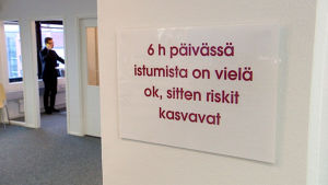 Taulu toimiston seinällä: 6h päivässä istumista on vielä ok, sitten riskit kasvavat