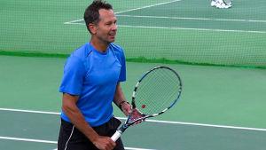 Ari Heinilä pelaa tennistä.