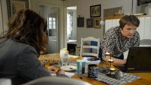Två kvinnor vid ett matbord. Den ena tittar på en laptop.