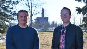 Två män står framför en gräsmatta. Solen skiner och i bakgrunden synns Sibbo kyrka.