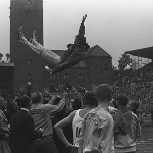 Ruotsalaiset urheilijat heittävät voiton kunniaksi kapteeniaan ilmaan Tukholman stadionilla 1960-luvulla