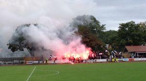 Bengaliska eldar brinner på en fotbollsläktare.