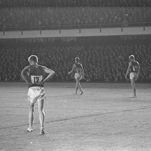 Juoksijoita kävelee Olympiastadionin nurmikolla Ruotsi-ottelussa 1960-luvulla