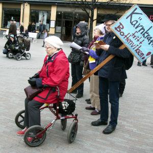 Demonstration mot kärnkraften i Umeå centrum, kvinna på rollator, man med plakat