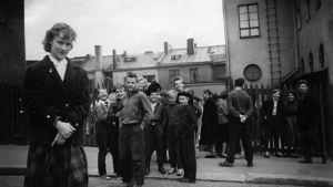 lapsia koulun pihalla, nuori tyttö etualalla, 1950-luku