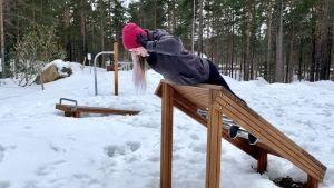 En kvinna i pink mössa och mörka kläder tränar ryggmuskler på en träställning utomhus. Det är snö på marken. I bakgrunden finns andra ställningar.