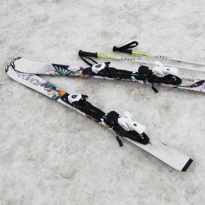Ett par slalomskidor och stavar på snö.
