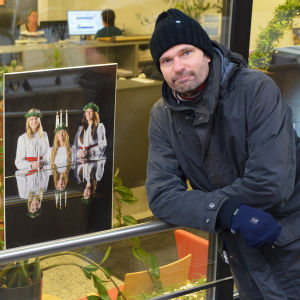 En man i mörk jacka och mössa står utanför Östnylands redaktion. Bredvid honom i fönstret hänger två stora fotografier där man ser lucia och hennes tärnor. På den ena bilden blåser tärnorna ut ljusen i lucias krona, på den andra sitter lucia bakom piano.
