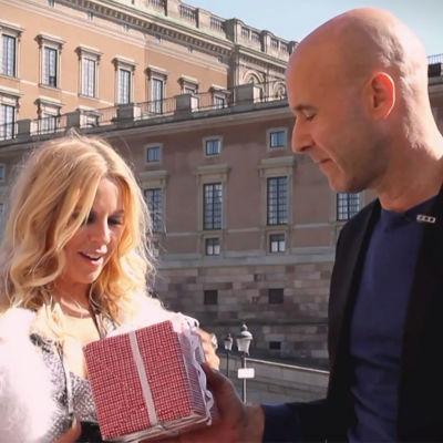 Mark Levengood ger ett paket åt Krista Siegfrids