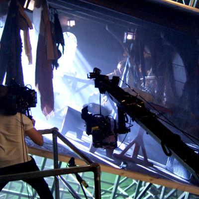 En kameraman filmar en scen i en kuliss som påminner om ett skepp.
