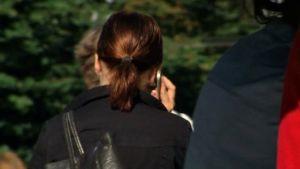 Nuori nainen puhuu kannettavaan puhelimeen. Kuvattu takaa.