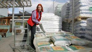 Nuori nainen lastaa multasäkkejä puutarhakaupassa