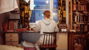 Nuori istuu huoneessaan.