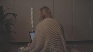 Nainen tietokoneella hämärässä kuvassa.