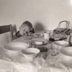 Pieni poika vanhassa valokuvassa on nukahtanut ruokapöydän ääreen.