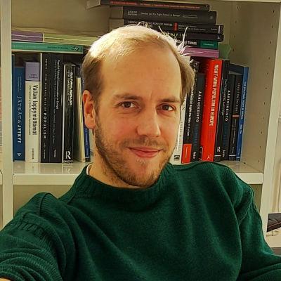 Georg Boldt sitter vid sitt arbetsbord framför en bokhylla.