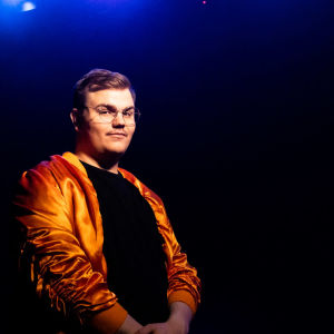 UMK-finalisti Aksel Kankaanranta seisoo tummansinisen taustan edessä kädet sylissä. Silmälasipäisellä Kankaanrannalla on yllään oranssi satiininen takki ja musta paita alla.