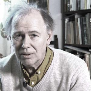 Anders Larsson med en stor bokhylla i bakgrunden.