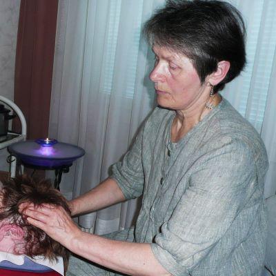 Yrittäjä Linda Pillai antaa reiki-hoitoa asiakkaalleen
