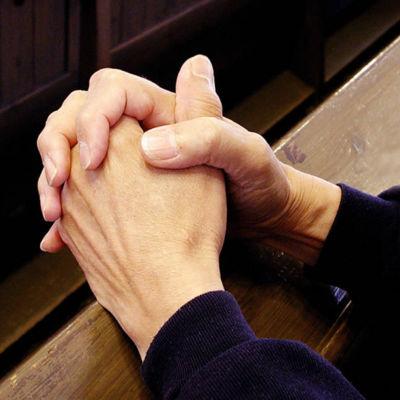 Händer knäppta till bön