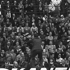 Suomalaismies johtaa yleisön huutokuoroa kaiteella seisten Tukholmassa 1960-luvulla